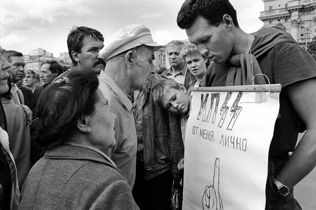 Giovane manifestante regge un cartello di insulti al PCUS. Piazza del Maneggio, Mosca